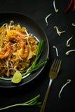 Vult de traditionele keuken van Thailand, Thaise, droge noedel, gebraden noedels, garnalen en zeevruchten, straatvoedsel, donkere royalty-vrije stock fotografie