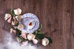 Vulten tekopp på en trätabell bland blommasidor och kronblad Arkivbild