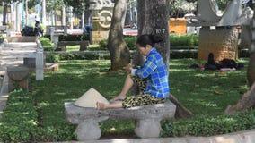 Vung Tau, Vietnam - 26 de enero de 2018: Un residente local descansa en el parque y se hace un masaje metrajes