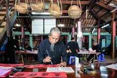 Man drawing calligraphy in Vietnam. VUNG TAU- VIETNAM: Old man with traditional black costume, white beard drawing calligraphy ancient distich in Long Son royalty free stock image