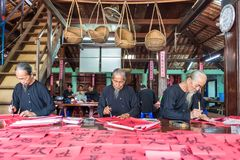Men drawing calligraphy in Vietnam. VUNG TAU- VIETNAM: Old men with traditional black costume, white beard drawing calligraphy ancient distich in Long Son stock image