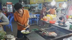 Vungtau, Vietnam - Januari 30, 2018: De onbekende verkoper bereidt de maaltijd van voedselzeevruchten bij een straat zijrestauran stock footage
