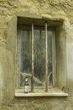 Vuoto bottiglia da birra lasciato in una vecchia finestra con le barre a Ragusa, Sicilia Italia fotografia stock