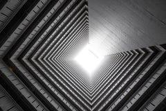 Vuoto concreto di costruzione astratto o tunnel della facciata con luce naturale alla fine nella progettazione di architettura di immagini stock