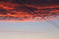 Vurige rode wolken bij zonsondergang in de avond stock fotografie