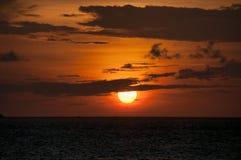 Vurige zonsondergang in de Maldiven: de rode schijf van de zon verlicht de hemel, de grijze strepen van wolken, het donkere water Stock Foto