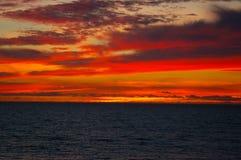 Vurige zonsondergang over donkere wateren van het overzees Stock Foto's