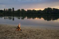 Vuur op de bank van de rivier bij zonsondergang Royalty-vrije Stock Foto