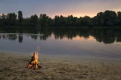 Vuur op de bank van de rivier bij zonsondergang Stock Afbeelding