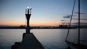 Vuurtoren bij zonsondergang in haven Burgas, de Zwarte Zee, Bulgarije Silhouetten van kranen bij zonsondergang stock video