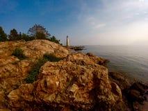 Vuurtoren in de rotsachtige kustlijn Stock Foto