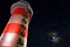 Vuurtoren door volle maan bij nacht Royalty-vrije Stock Afbeeldingen