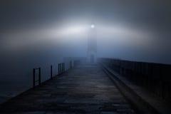 Vuurtoren in een mistige nacht Stock Foto's