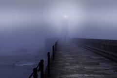 Vuurtoren in een mistige nacht Stock Afbeeldingen