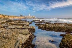 Vuurtoren en rocksn in Vreedzame kust Stock Afbeeldingen