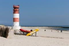 Vuurtoren en toeristen die op verbindingen letten bij strand van Duits eiland Stock Afbeelding