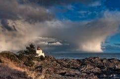 Vuurtoren langs Rotsachtige Kust met Onweerswolken in Afstand Royalty-vrije Stock Afbeeldingen