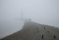 Vuurtoren in mist stock afbeelding