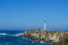 Vuurtoren op een klip op de oceaan met golven op een mooie de zomerdag stock fotografie