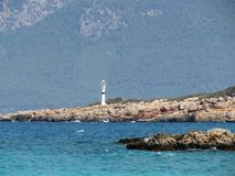 Vuurtoren op een rotsachtig eiland in de Middellandse Zee Kleurrijk zeegezicht stock fotografie