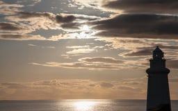 Vuurtorensilhouet in humeurige zonsondergang Royalty-vrije Stock Afbeeldingen