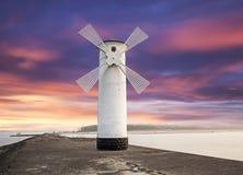 Vuurtorenwindmolen met dramatische zonsonderganghemel. Royalty-vrije Stock Afbeeldingen
