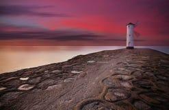 Vuurtorenwindmolen met dramatische zonsonderganghemel Royalty-vrije Stock Foto's