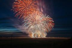 Vuurwerk over de stad Multi-colored vuurwerk tegen de achtergrond van de zonsonderganghemel stock fotografie