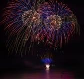 Vuurwerkvertoning over overzees met bezinningen in water Royalty-vrije Stock Foto's