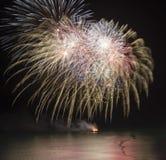 Vuurwerkvertoning over overzees met bezinningen in water Stock Foto