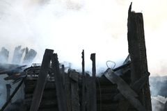 vuurzee ruïnes en overblijfselen van een gebrand blokhuis Gebrand verkoold brandhout in dikke rook royalty-vrije stock foto