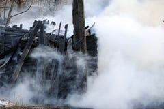 vuurzee ruïnes en overblijfselen van een gebrand blokhuis Gebrand verkoold brandhout in dikke rook stock foto's