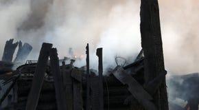 vuurzee ruïnes en overblijfselen van een gebrand blokhuis Gebrand verkoold brandhout in dikke rook stock fotografie