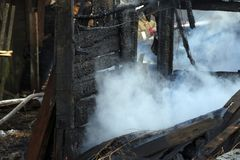 vuurzee ruïnes en overblijfselen van een gebrand blokhuis Gebrand verkoold brandhout in dikke rook stock foto