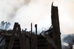 vuurzee ruïnes en overblijfselen van een gebrand blokhuis Gebrand verkoold brandhout in dikke rook stock afbeelding