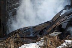vuurzee ruïnes en overblijfselen van een gebrand blokhuis Gebrand verkoold brandhout in dikke rook stock afbeeldingen