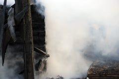 vuurzee ruïnes en overblijfselen van een gebrand blokhuis Gebrand verkoold brandhout in dikke rook royalty-vrije stock afbeelding