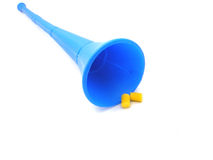 Vuvuzela horn and earplugs. Closeup of traditional blue South African Vuvuzela blowing horn used by soccer fans with two earplugs, isolated on white background Stock Photo