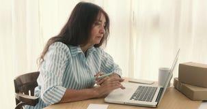 Vuxen affärskvinna som arbetar på tabellen arkivfilmer
