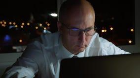 Vuxen affärsman som äntligen arbetar till aftonen för bärbar datordator i mörkt kontor stock video