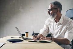 Vuxen affärsman som arbetar på det moderna coworking kontoret Säker man som använder den moderna mobila bärbara datorn royaltyfria foton