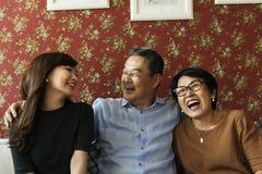 Vuxen affektion som förbinder den tillfälliga gladlynta familjen arkivbilder
