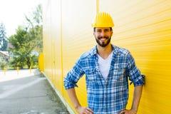 Vuxen arbetare med hjälmen på den gula väggen Arkivbild
