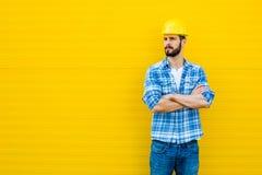 Vuxen arbetare med hjälmen på den gula väggen Arkivfoton
