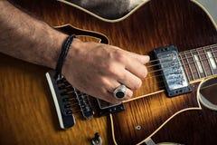 Vuxen caucasian gitarriststående som spelar den elektriska gitarren på grungebakgrund Övre instrumentdetalj för slut musik royaltyfria bilder