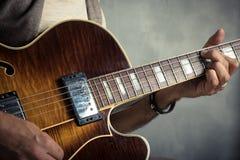Vuxen caucasian gitarriststående som spelar den elektriska gitarren på grungebakgrund Övre instrumentdetalj för slut musik arkivfoton