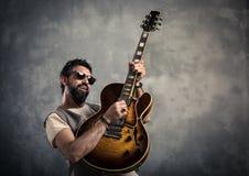 Vuxen caucasian gitarriststående som spelar den elektriska gitarren på grungebakgrund Modernt begrepp för musiksångare royaltyfri bild