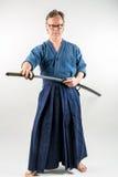 Vuxen caucasian man med exponeringsglas som utbildar Iaido som drar ett japanskt svärd med fokuserad blick Royaltyfri Bild