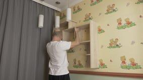 Vuxen caucasian vit manpassformbokhylla till väggen i barnrum Den manliga mannen försöker på bokhyllan i barnrum diy begrepp arkivfilmer