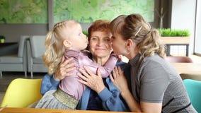 Vuxen dotter och liten sondotter att kyssa deras farmor lager videofilmer